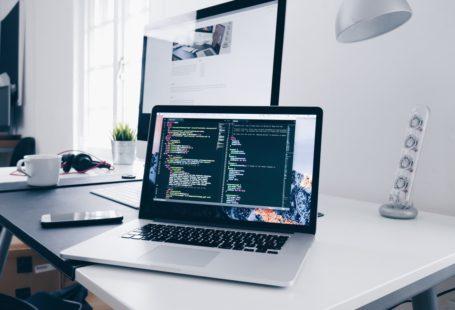 Un ordinateur posé sur un bureau, où on peut lire une page de code