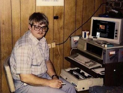 Un jeune développeurs nous regarde, il est assis devant son ordinateur. Il a l'air assez geek avec ses grosses lunettes de vue, il fait très seventies.