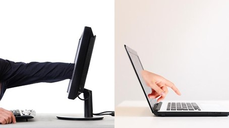 Une main de développeurs traverse l'écran d'un ordinateur fixe et ressort par l'écran d'un ordinateur portable